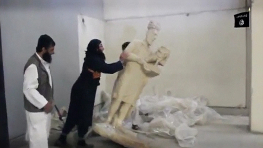 A man topples a statue in a museum at a location said to be Mosul